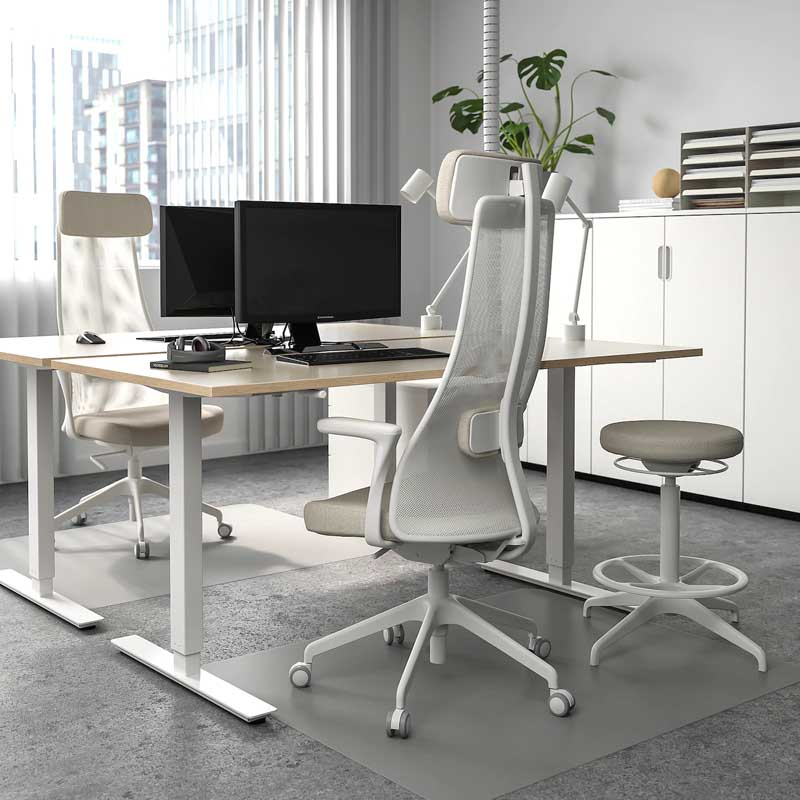 An ikea Skarsta Sit Stand Desk with white legs and beige top in an office enironment.